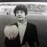 Zdjęcie czarno-białe. Sędzia żużlowa Irena Nadolna-Szatyłowska na stadionie. Trzyma puchar.